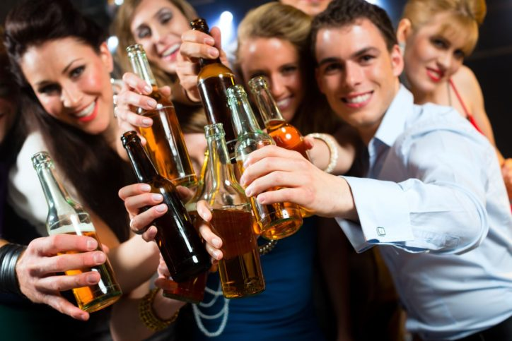young-people-in-club-or-bar-drinking-beer-out-of-a-beer-bottle-and-have-fun