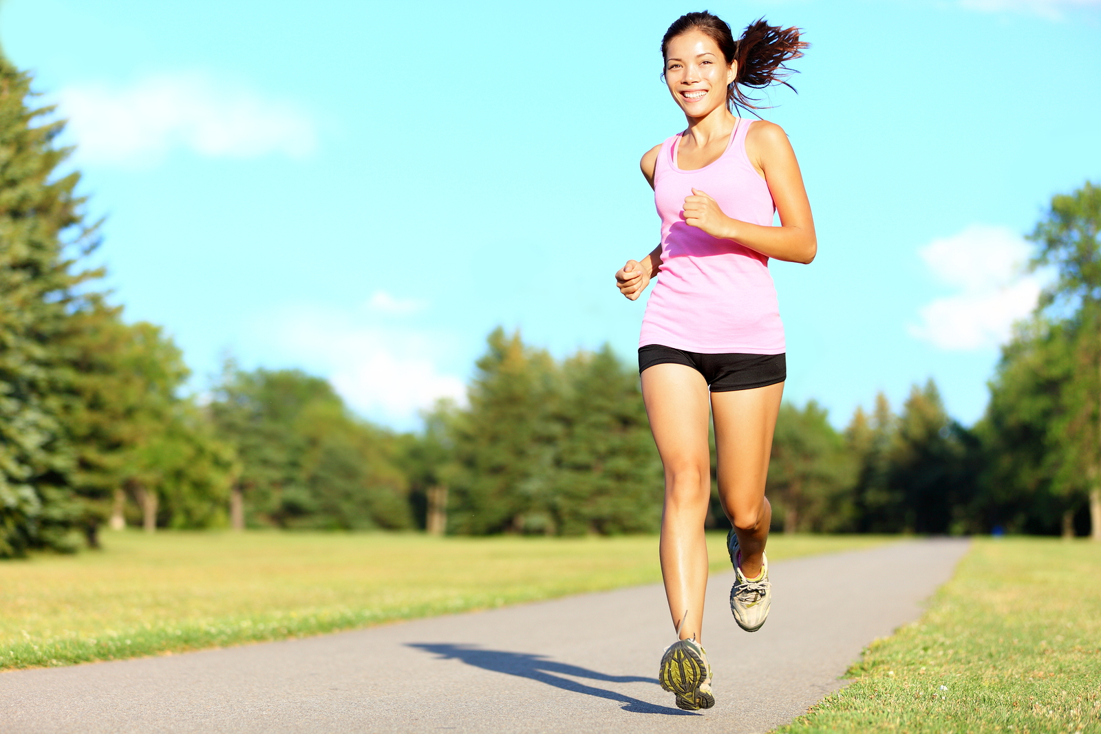 Sport fitness woman running in park on summer day. Asian female