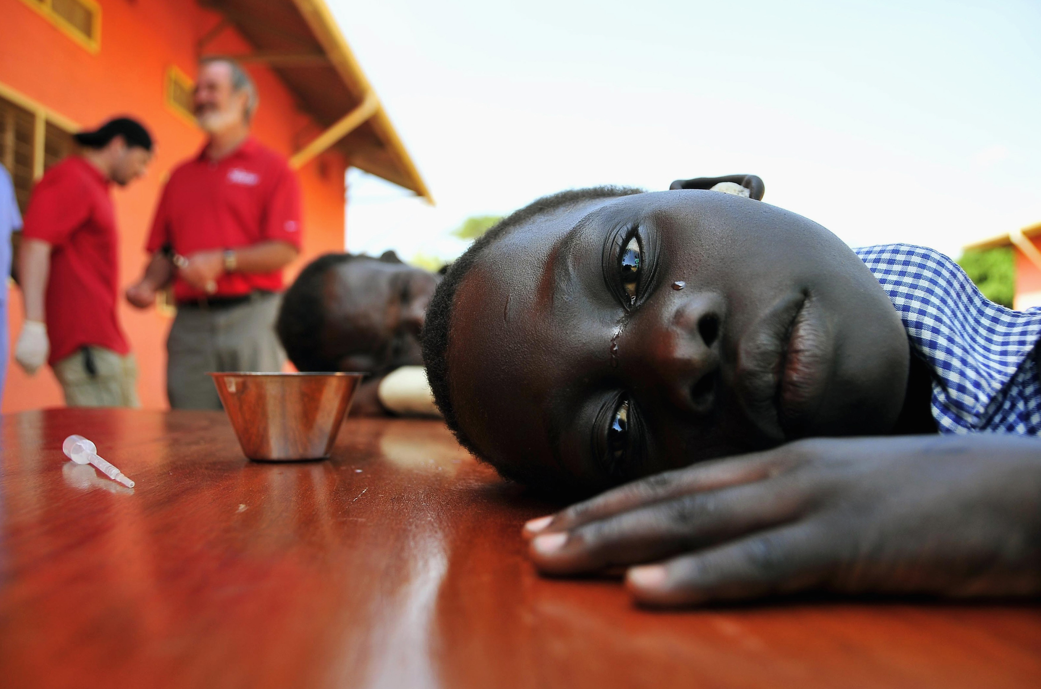 A girl with hearing challenges cries after her ears were cleaned during an event held by Starkey Hearing Foundation at St. Monica in Gulu