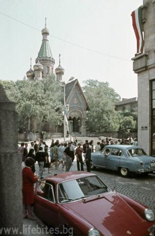 София, лятото на 1968 г. Минувачи зяпат червено порше, паркирано на столичната улица Бенковски. На заден план се вижда един от хилядите транспаранти, с които е окичен града по време на Младежкия фестивал.