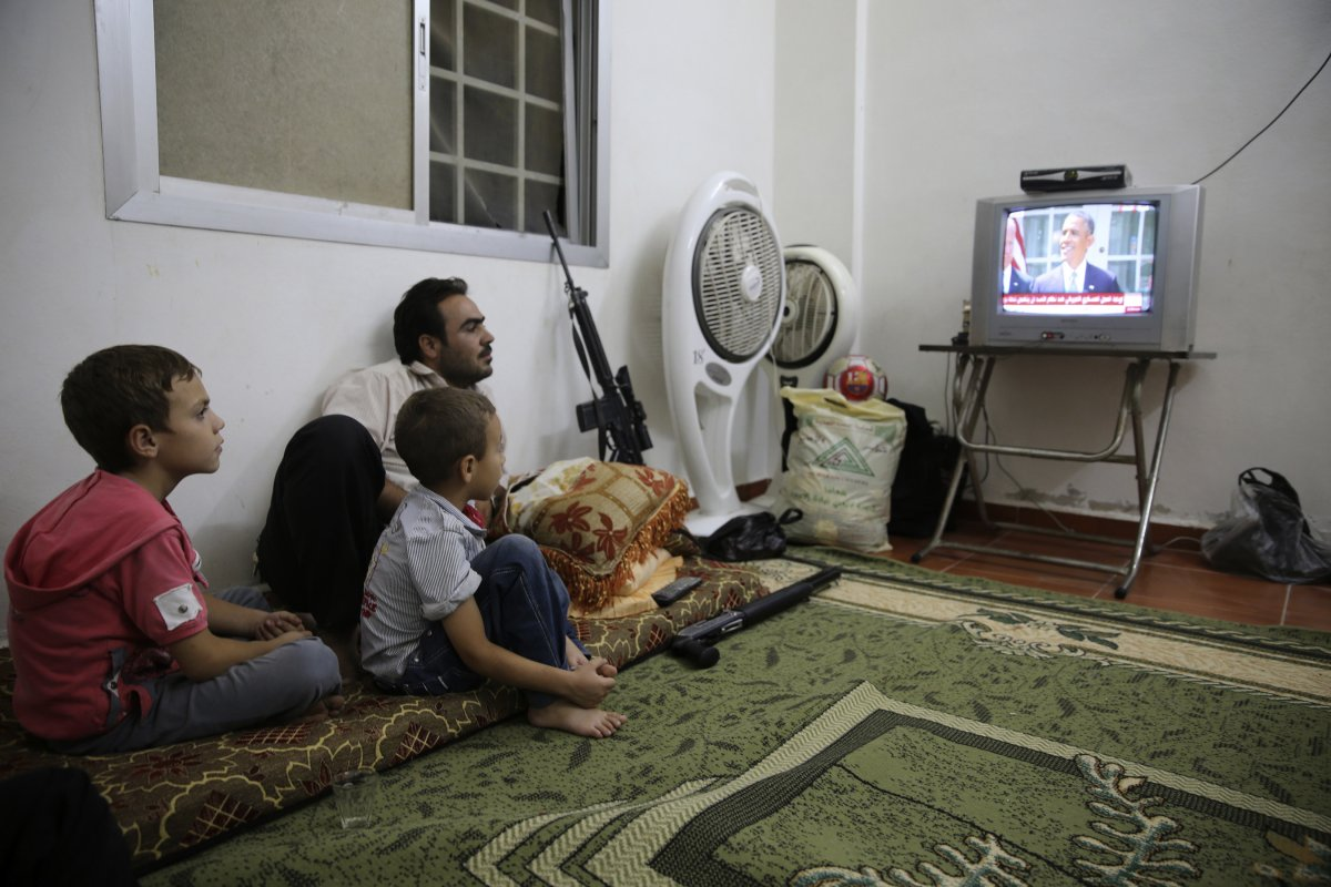 a-free-syrian-army-fighter-watches-a-speech-by-barack-obama-from-ghouta-syria