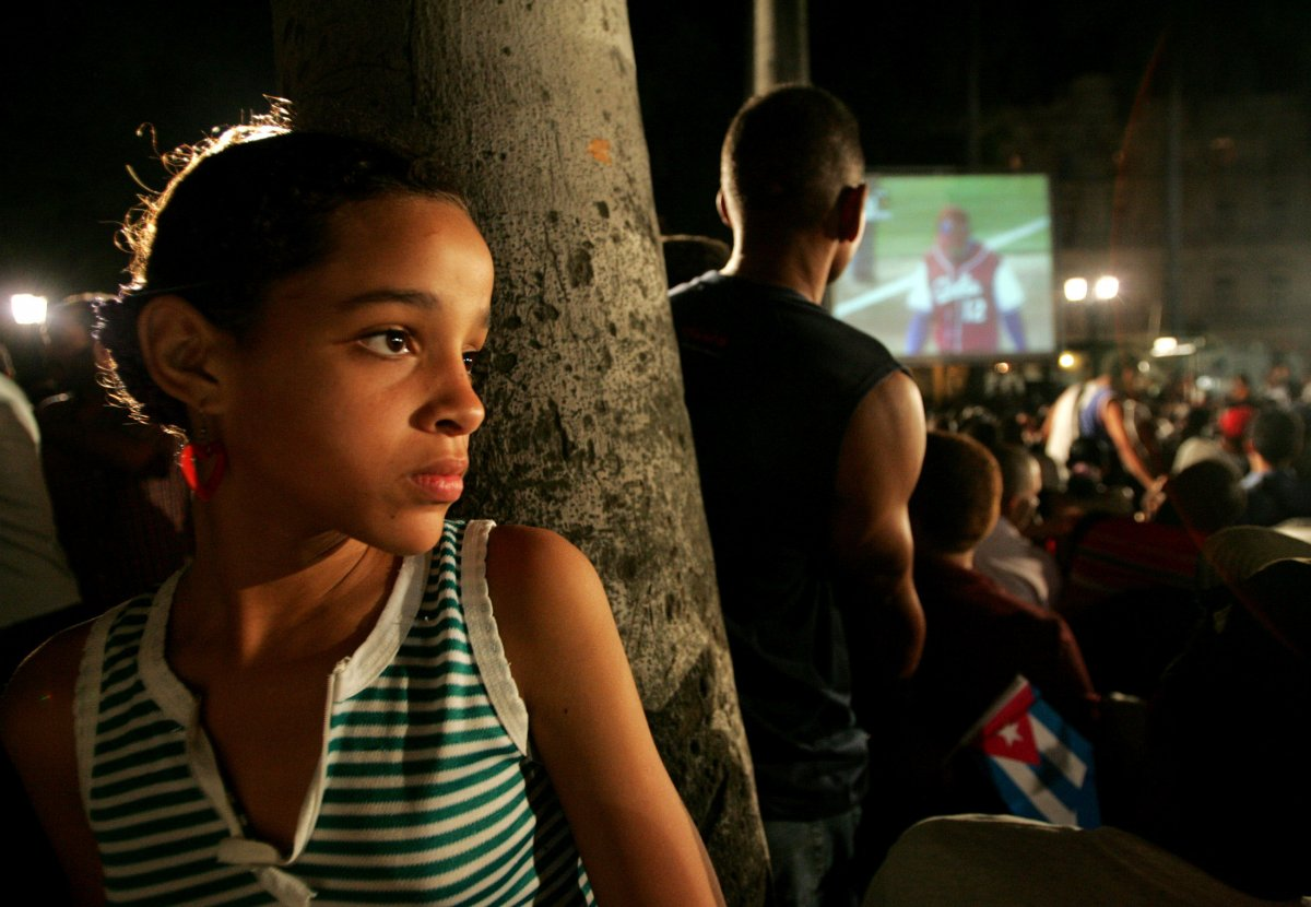 a-girl-leans-against-a-tree-in-havana-while-a-group-has-gathered-nearby-to-watch-their-countrys-team-compete-in-the-world-baseball-classic