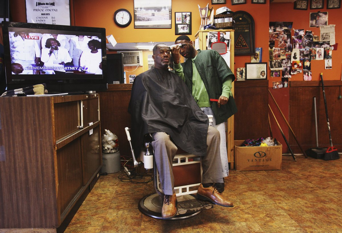a-man-gets-his-haircut-in-newark-new-jersey-while-the-tv-plays-in-the-background