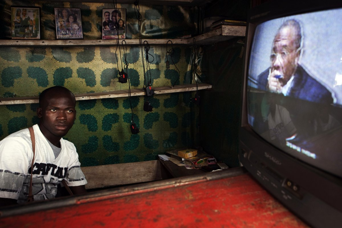 a-street-vendor-watches-a-live-broadcast-as-the-now-former-liberian-president-charles-taylor-is-convicted-of-aiding-and-abetting-war-crimes-in-2012