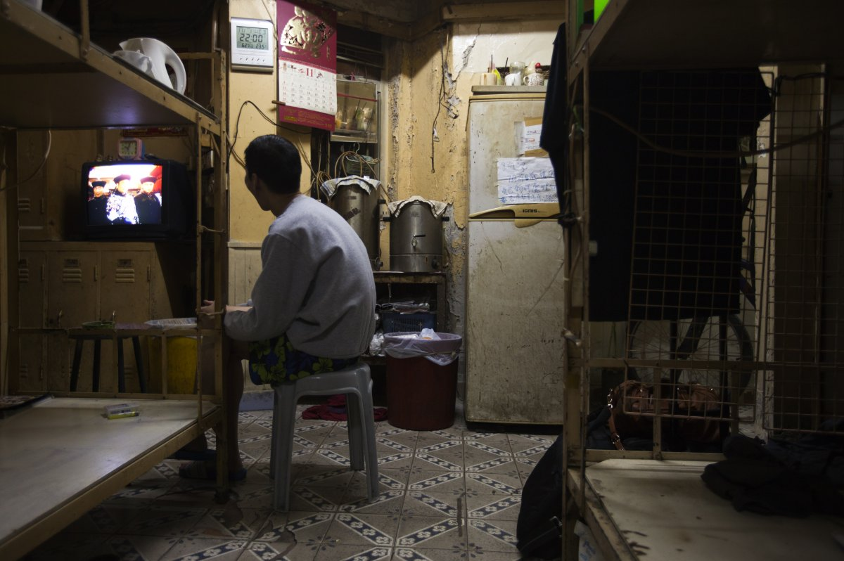 in-front-of-his-bed-in-hong-kong-a-local-watches-tv-in-the-dim-light-of-a-home-that-he-rents-for-167-a-month