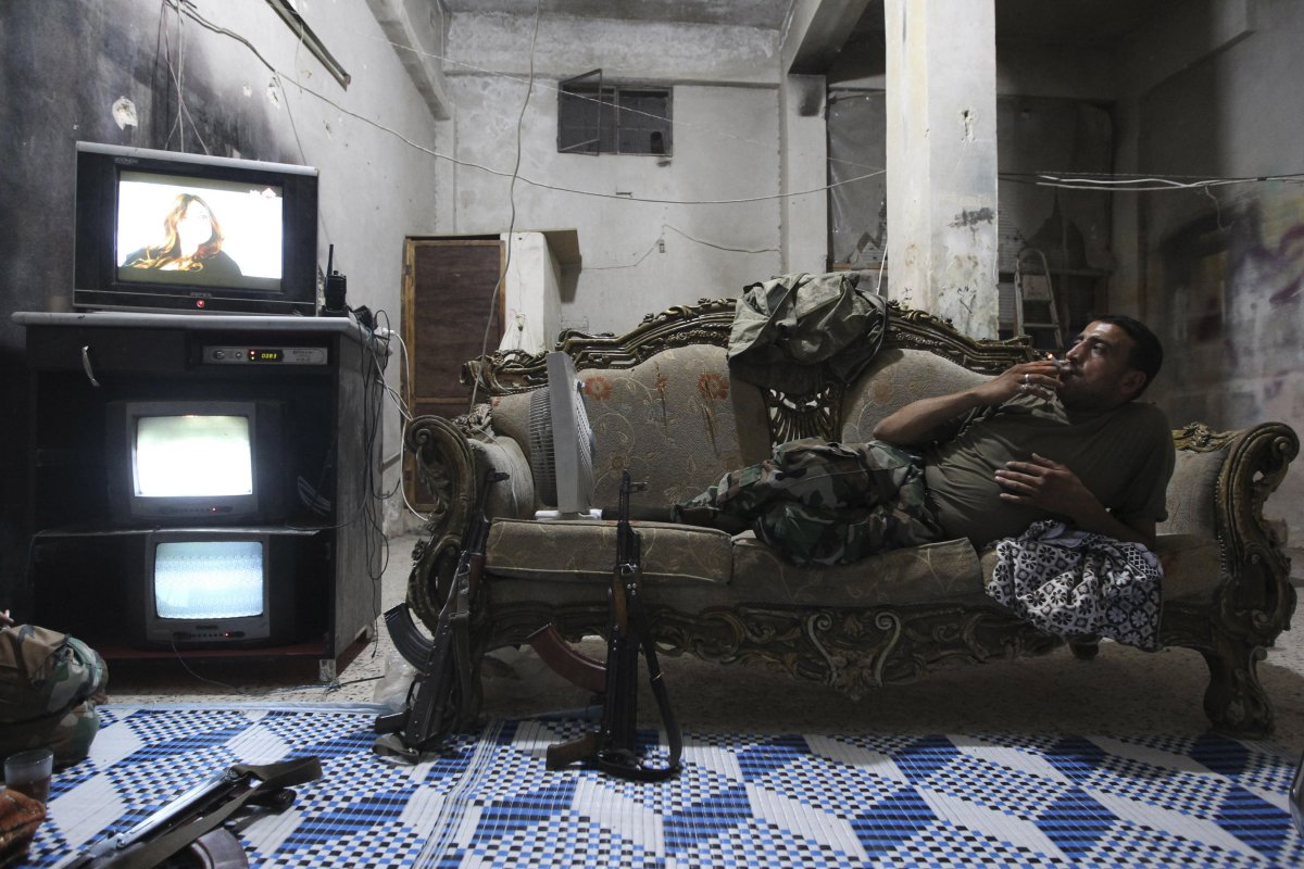 inside-a-room-in-aleppos-karm-al-jabal-district-a-free-syrian-army-fighter-kicks-back-while-watching-tv-and-surveillance-monitors
