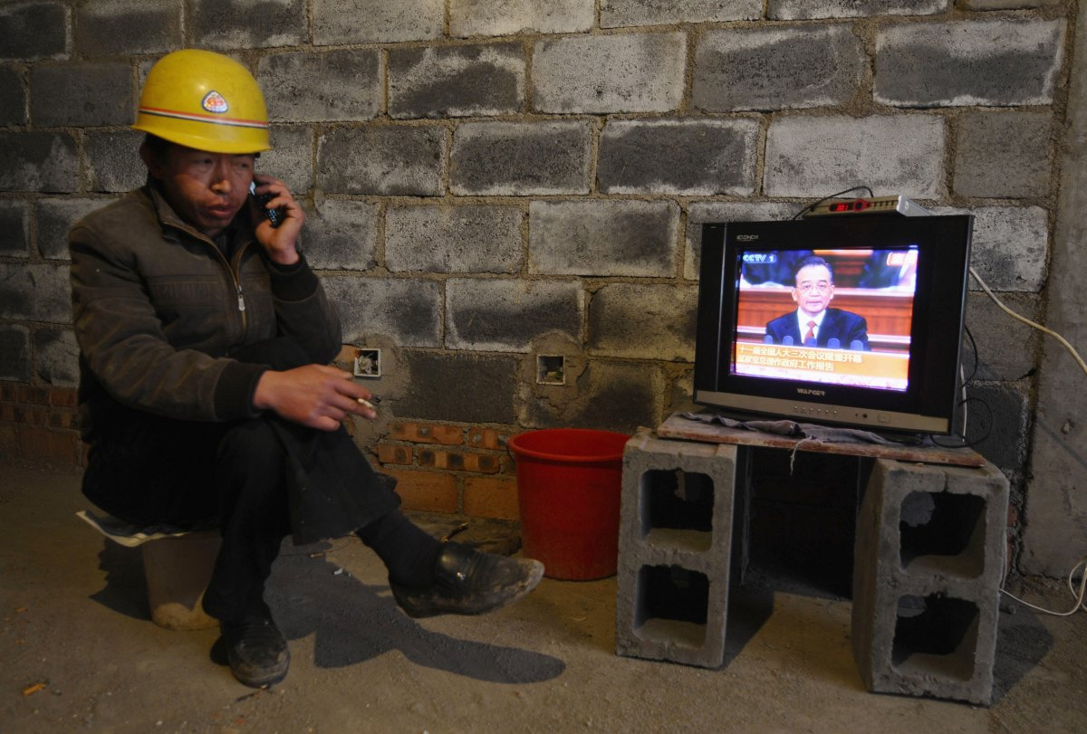 simultaneously-talking-on-the-phone-and-smoking-a-cigarette-a-labor-worker-in-changzhi-china-catches-a-government-broadcast-on-tv