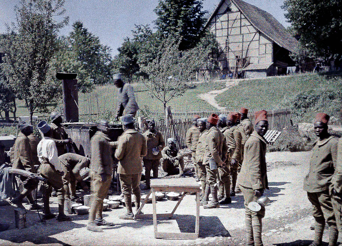 A group of Senegalese soldiers serving in the French Army as infantrymen is having lunch in Saint-Ulrich, Department Haut-Rhin, Region Alsace. 16th June 1917. Western Front. World War I. Autochrome LumiËre. Photo: Paul Castelnau (1880-1944). France. (Photo by Galerie Bilderwelt/Getty Images)
