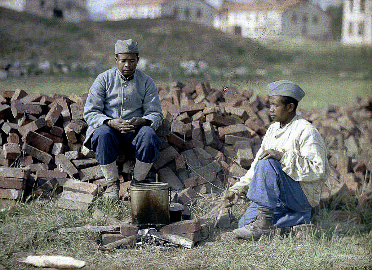Two French soldiers from Africa are heating up a meal on an outdoor fireplace made from brick. World War I, Western Front. 1917. Color photo (Autochrome LumiËre) by Fernand Cuville (1887-1927). Soissons, Aisne, France. (Photo by Galerie Bilderwelt/Getty Images)