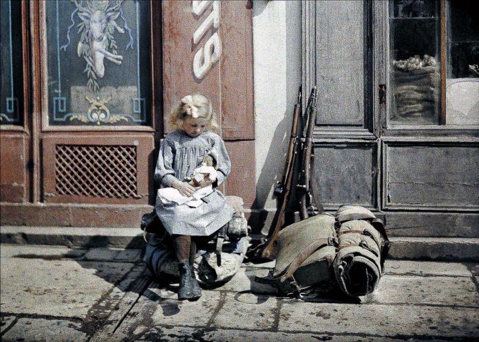 Момиче с кукла. До него са две пушки и раница на войници от Западния фронт.