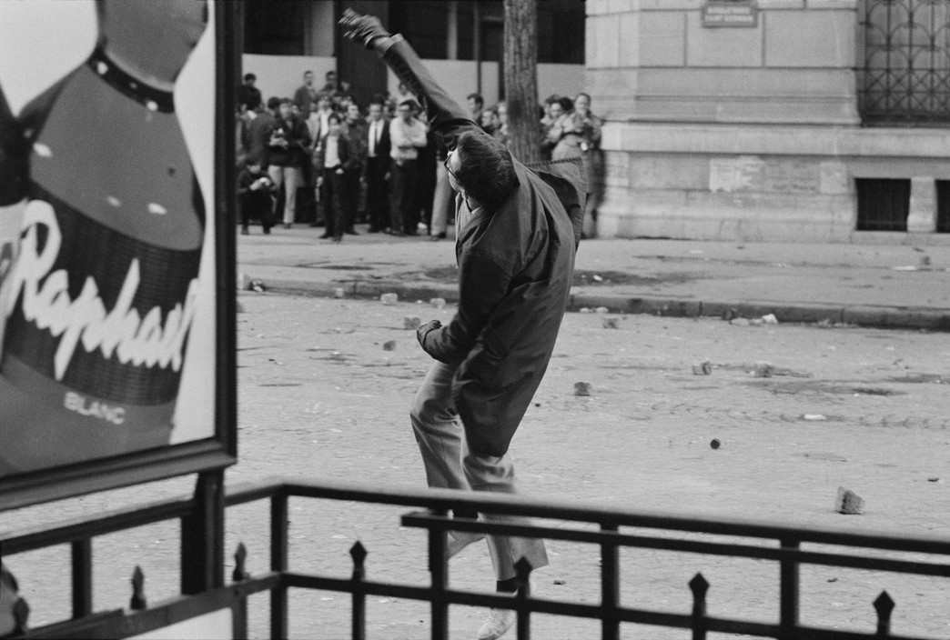A young man throwing a rock on the boulevard Saint Germain.