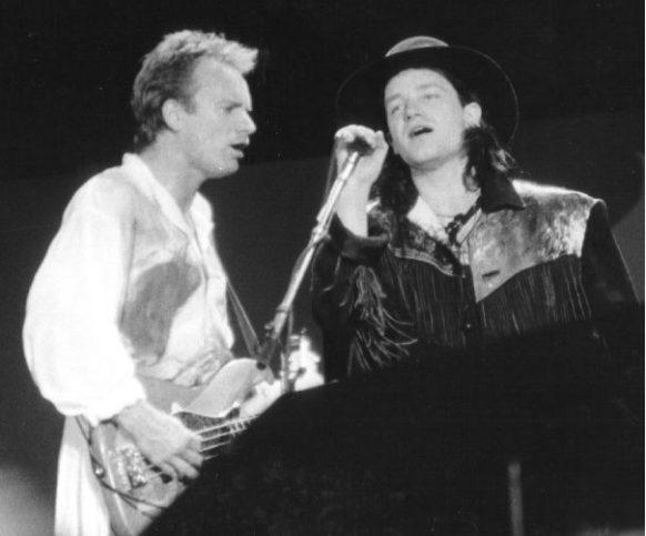 Две живи легенди - големи музиканти и големи хора - Стинг и Боно на една сцена през 1986 г. Снимка: Steven Toole - Own work, CC BY-SA 3.0, Link